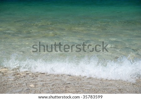 Tropical sand beach with sea waves and stones.