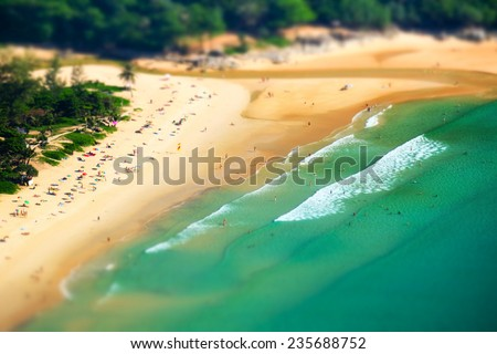 Tropical sandy beach landscape from high view point tilt shift effect. Beautiful turquoise ocean and people relaxing in waives. Rawai, Ya Nui beach, Phuket, Thailand - stock photo