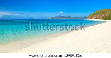 Tropical sandy beach Malcapuya at summer sunny day. Panorama - stock photo