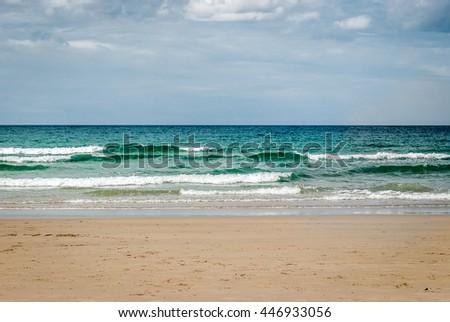 Tropical sandy beach with clear sky at the low tide. Atlantic ocean Spain. Blue skies, clouds over tropical beach with sand in Mediterranean, Tropic or Atlantic sea in Spain, Croatia, Italy or Greece. - stock photo