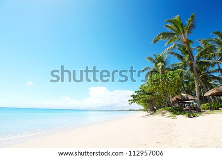 Tropical sandy beach with palm trees at sunny day. South of Bali, Jimbaran beach - stock photo