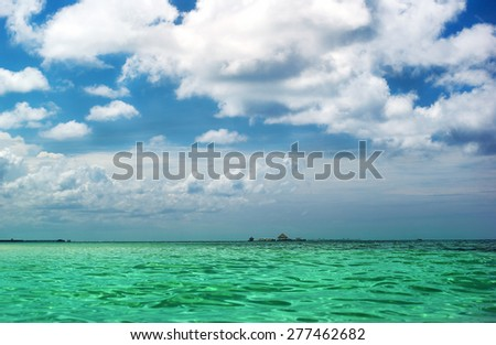 Tropical seascape. Bright green water and blue sky - stock photo