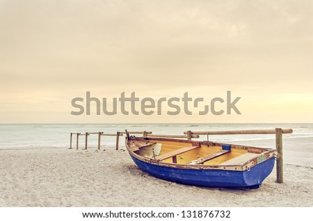 Tropical Seascape with a wooden, old and broken yellow blue boat on white beach on warm sunset. - stock photo