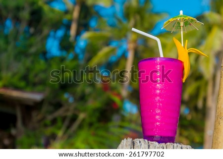 tropical shake, refreshment drink in decorated glass on tropical background - stock photo