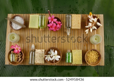 Tropical spa setting on wooden mat with big leaf background