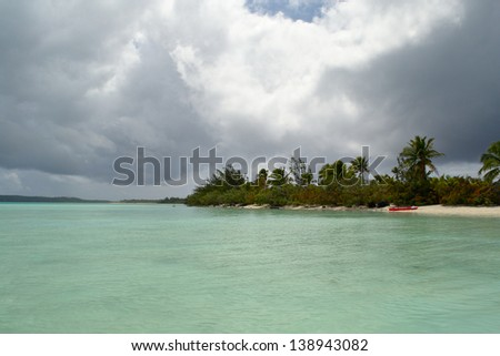 Tropical stormy weather at the horizon while exploring the gorgeous lagoon of Aitutaki by canoeing. Location: Cook Islands - stock photo