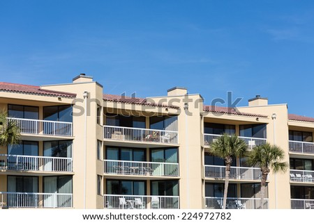 Tropical stucco condos with furniture on balconies - stock photo