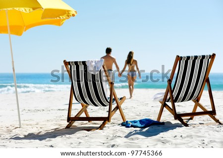Tropical summer beach holiday couple walk towards the ocean holding hands while on honeymoon vacation - stock photo