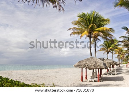 Tropical summer beach resort with palm trees and cabanas in Miami Beach Florida on a beautiful summer day with colorful ocean waters of the Atlantic, pristine sands and cloudy sky. Copy space. - stock photo