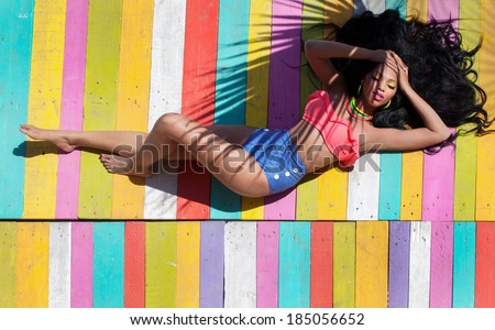 Tropical summer holiday fashion vogue concept - african american woman on a wooden pier background - stock photo
