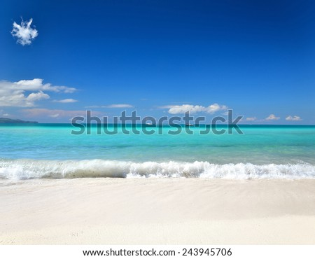 Tropical sunny beach and blue sky background -- Waves on a sandy beach comes to shore  - stock photo