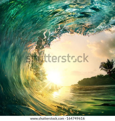 Tropical sunset background. Beautiful colorful ocean wave crashing closing near sand beach with palm tree - stock photo
