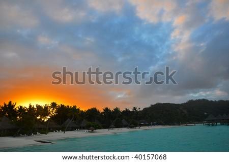 Tropical sunset over the island of Bora Bora in Tahiti. - stock photo