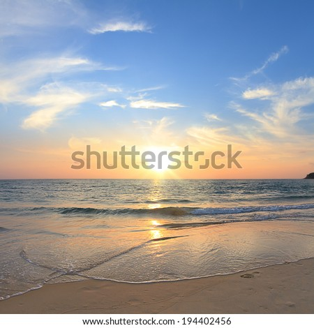 Tropical sunset scenery. Calm water and a beach with footprint on sand - stock photo