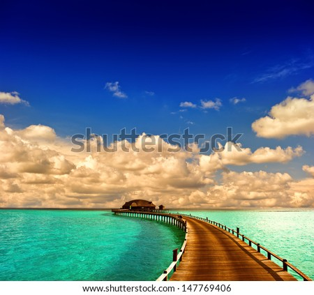 tropical sunset seascape. overwater bungalow with jetty with dramatic blue sky - stock photo