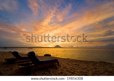 Tropical sunset - two beach chairs can be seen in the foreground.
