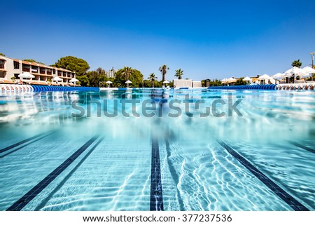 Tropical swimming pool views over the water and under water. - stock photo