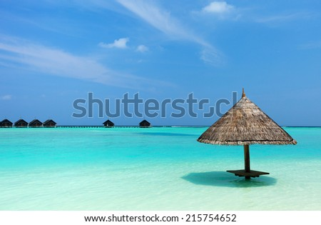 Tropical thatch umbrella on a beautiful beach at Maldives - stock photo