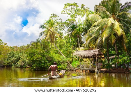 Tropical thickets mangrove forest on the island of Sri Lanka. Traditional fisherman in dugout canoe in Sri Lanka. - stock photo