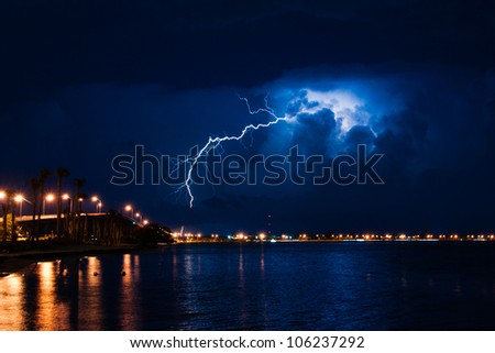 Tropical thunderstorm at night over Miami with massive lightning bolt - stock photo