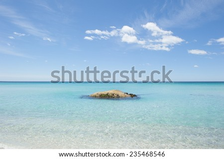 Tropical turquoise Pacific Ocean water with single rock at beach at Bay of Fire in Tasmania, beautiful scenery, popular holiday destination for tourists, copy space. - stock photo