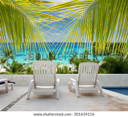 Tropical vacation. Seaview from luxury resort balcony through palm tree leafs - stock photo