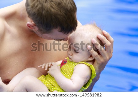 Tropical vacation with an infant. Small baby girl is swimming in the pool with daddy for the first time. Father is holding baby and talking to her.Three months old baby. - stock photo