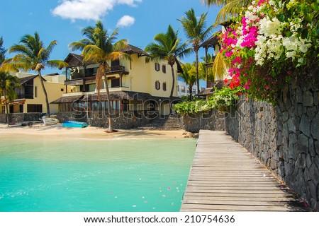 Tropical villa houses on paradise beach in Grand Baie coastal village, Mauritius island - stock photo