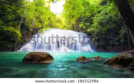 Tropical waterfall in Thailand, nature photography. Fresh water mountain river in wild green jungle forest. Scenic and peaceful Asia nature background of beautiful blue water pool and creek cascade - stock photo