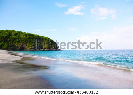 Tropical white sandy beach with rocky mountains and clear water of Indian ocean in Bali.  - stock photo
