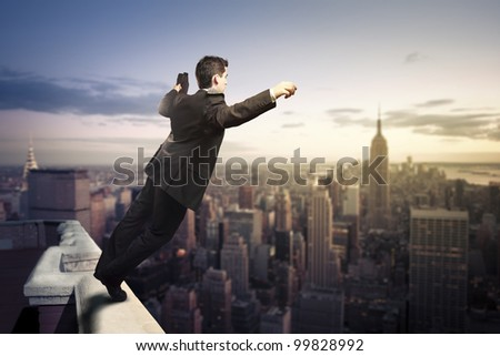 Troubled businessman jumping from the top of a building
