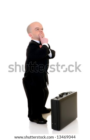 Troubled little businessman, dwarf in a formal suit with bow tie next to  suitcase, studio shot, white background
