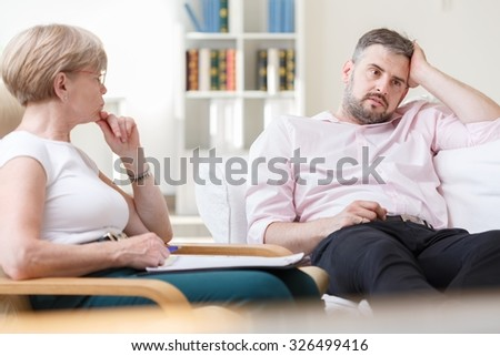 Troubled man talking with psychologist during therapy - stock photo