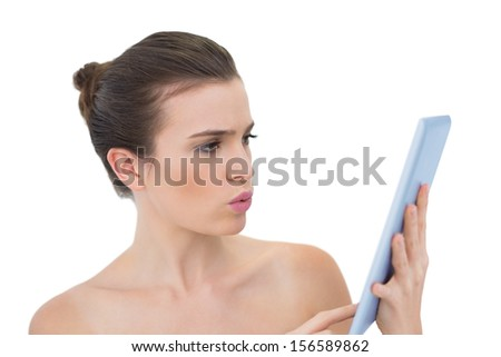 Troubled natural brown haired model using a tablet pc on white background - stock photo