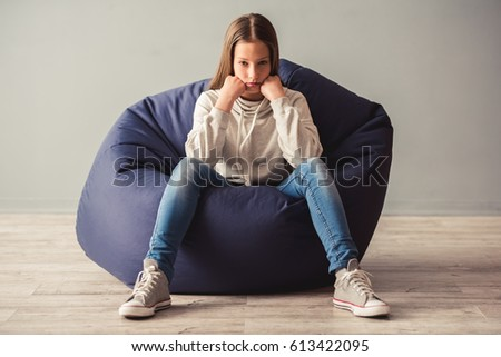 Troubled Teenage Girl Is Sitting On Bean Bag Chair And Looking At Camera