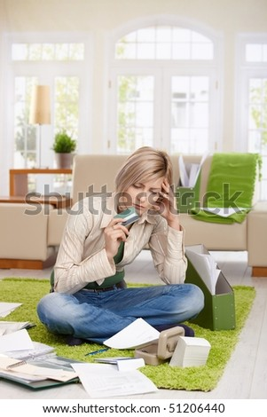 Troubled woman sitting on floor with crossed legs, looking at documents holding credit card in living room. - stock photo