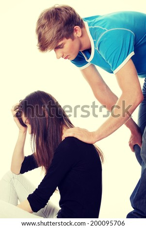 Troubled young girl comforted by her boyfriend. - stock photo