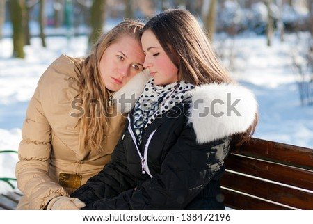 Troubled young girl comforted by her friend on winter outdoors background - stock photo