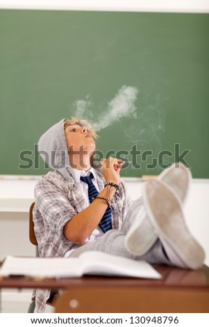 troublesome teen boy smoking in classroom - stock photo