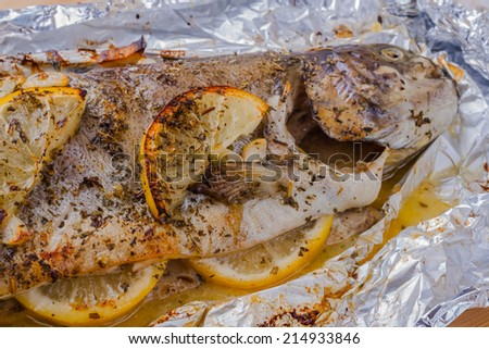Trout fish baked with lemon, garlic and herbs - stock photo