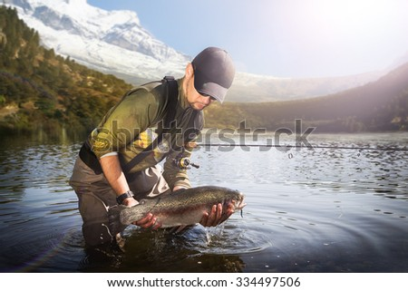 Trout-fishing on mountain river  - stock photo