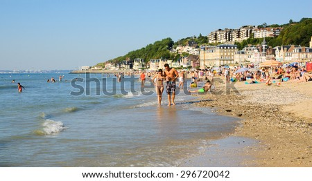 TROUVILLE-SUR-MER, FRANCE - JULY 10, 2015: People relax on the beach. Trouville-sur-Mer and nearby Deauville are popular summer resorts in Normandy region.