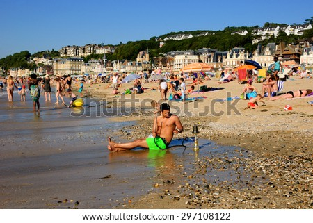 TROUVILLE-SUR-MER, FRANCE - JULY 10, 2015: Unidentified young man relaxing with hookah on the beach. Trouville-sur-Mer and nearby Deauville are popular summer resorts in Normandy region. - stock photo