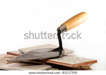 trowel lying on the tiles - stock photo