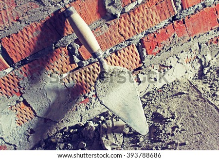 Trowel on a brick wall background - stock photo