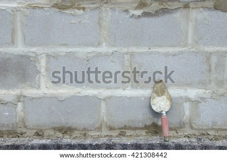 Trowel on cinder block gray background. against the background of the brickwork is trowel - stock photo
