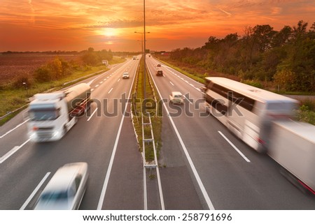 Truck and bus in motion blur on the highway towards the setting sun. Rush hour on the freeway near Belgrade - Serbia. - stock photo