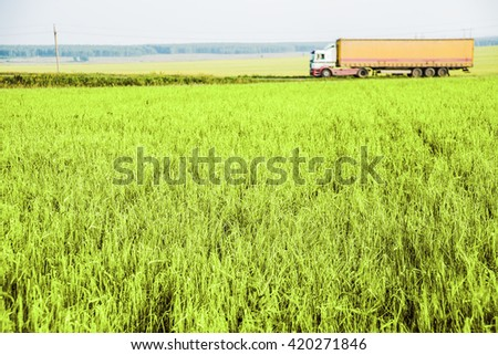 Truck driving on a rural road. View from the side of the road. Wheat field. transportation and row food background.  - stock photo