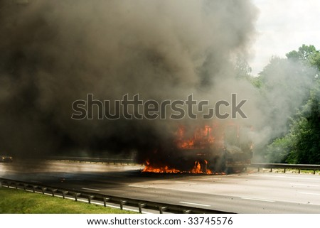 truck explosion on the road with a lot of fire and smoke - stock photo