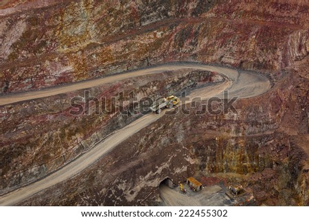 Truck leaves hole in ground and drives along a winding path inside an open cast mine in New South Wales, Australia.  - stock photo